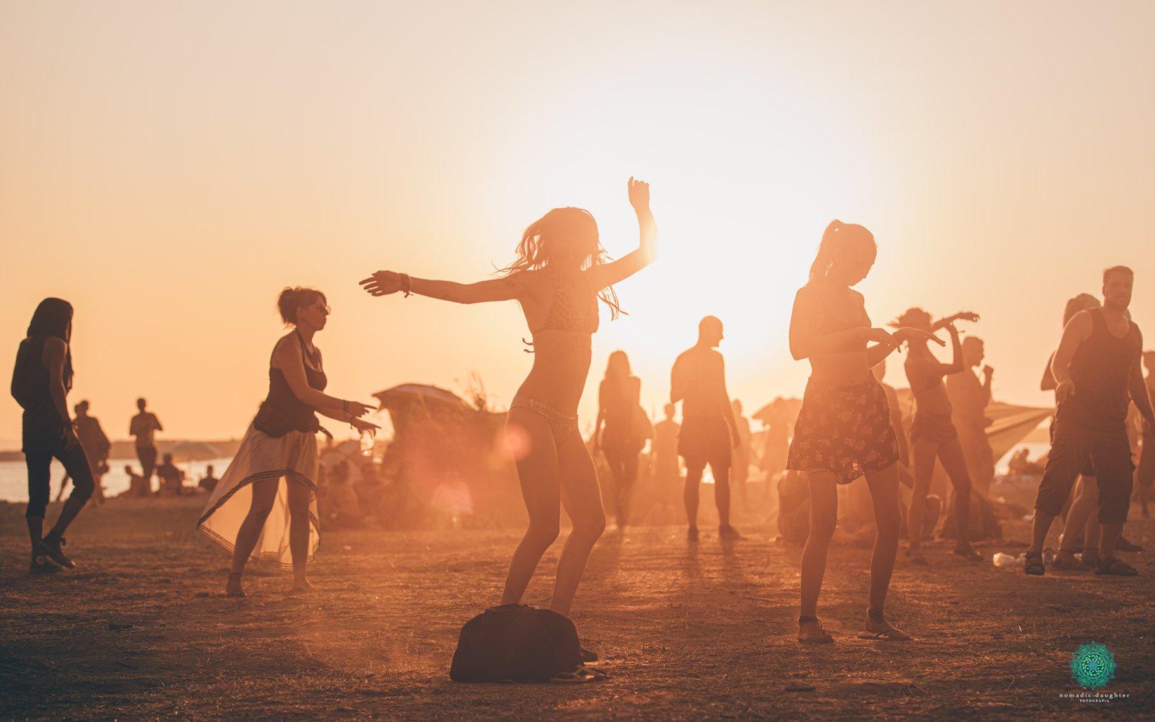 אנשים רוקדים על החוף ביוון בפסטיבל free earth